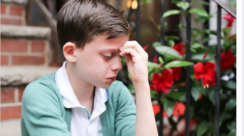 Ein kleiner Junge sitzt auf einer Stufe und weint