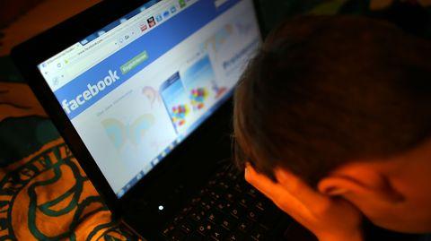 Ein Mann sitzt deprimiert vor seinem Rechner. Facebooks Seite ist geöffnet.