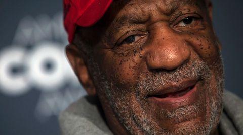 Bill Cosby trägt einen Stoppelbart, eine Schirmmütze und einen Kapuzenpullover. Sein Lächeln wirkt angestrengt.