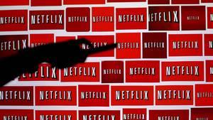 Eine Hand mit Fernbedienung ist vor einer Wand aus Netflix-Logos zu sehen.