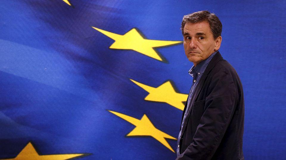 Euklid Tsakalotos steht vor einer Projektion der griechischen und europäischen Flagge