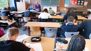 Schüler sitzen konzentriert an ihren Pulten