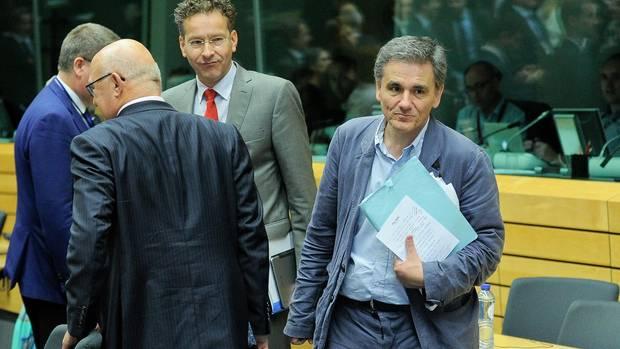 Euklid Tsakalotos hält steht nach dem Treffen der Euro-Finanzminister auf. Sein Notizzettel klemmt sichtbar an seiner Mappe