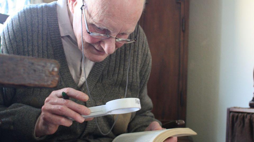 Eberhard hält eine Lupe in der Hand und liest ein Buch