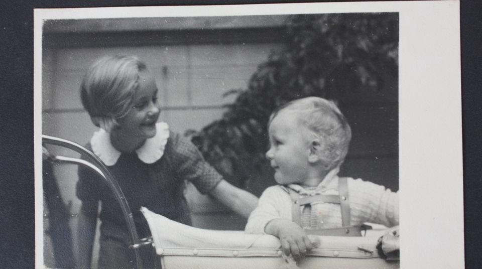 Eberhard sitzt im Kinderwagen, Jutta streichelt ihm den Rücken