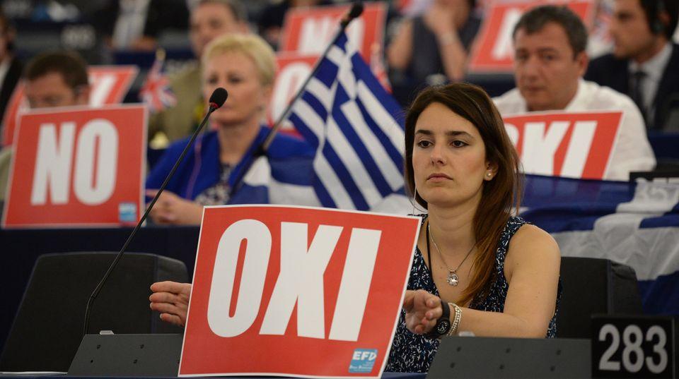 """Etwa 15 Abgeordnete halten vor sich Schilder, auf denen """"Oxi"""" oder """"Nein"""" geschrieben steht"""
