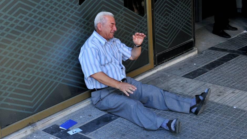 Griechenland-Krise: Ein weinender Rentner sitzt vor einer Bank. Er hatte kein Geld mehr bekommen.