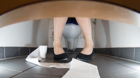 Eine Frau sitzt auf der Toilette. Neben ihr ist eine abgerollte Klorolle