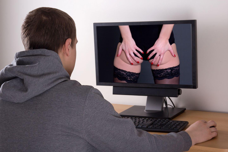Ein junger Mann schaut auf einen Computerbildschirm, auf dem eine Frau in Dessous von hinten zu sehen ist