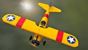 Eine Boeing Stearman fliegt über offenes Wasser