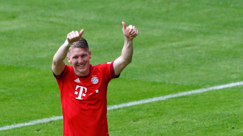 Bastian Schweinsteiger im roten FC Bayern Trikot hält auf dem Fußballplatz grinsend seine Daumen in die Luft