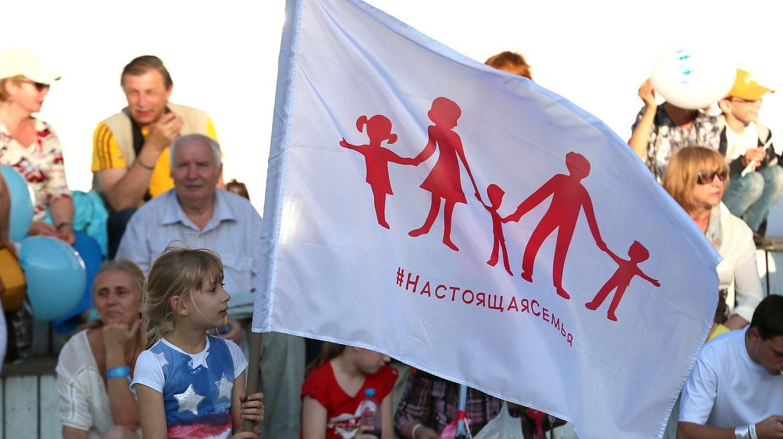 Ein Mädchen hält die neue russische Familien-Flagge in die Höhe