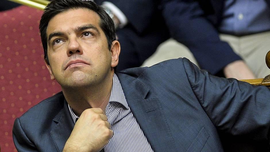 Alexis Tsipras lehnt sich auf seinem Sitz im griechischen Parlament zurück, fasst sich an den Hemdkragen und schaut nach oben.