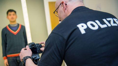 Ein Polizist kontrolliert einen Flüchtling