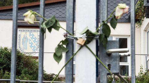 Am Tor zum Gelände der Schützenhalle in Marsberg im Sauerland sind zwei gekreuzte, weiße Rosen befestigt.