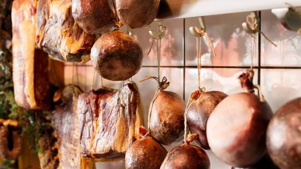Wie an einer Garderobe hängen Neumeiers Meisterwerke im Verkaufsraum seiner Metzgerei - Zungenblut- und Zungenleberwurst in Schweinsblasen, Nusschinken, Schinkenspeck. Und wie das duftet! Geräuchert wird im Naturrauch über Buchenspänen.