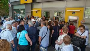 Menschen stehen vor einer geschlossenen Bank in Athen