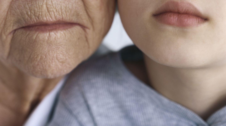 Eine alte Frau und ein junges Mädchen Wange an Wange