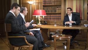 Alexis Tsipras sitzt an seinem Schreibtisch zwei Journalisten des Senders ERT gegenüber