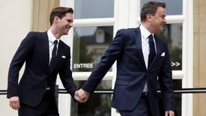 Der luxemburgische Ministerpräsident Xavier Bettel hält seines Ehemanns Gauthier Destenay an der Hand, beide tragen Anzüge.