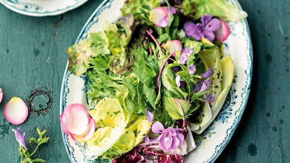 Teller mit buntem Salat und Vinaigrette auf einem Holztisch
