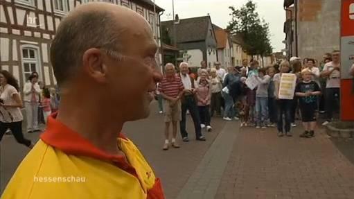 Paketzusteller Helmut Becker schaut auf 200 Demonstranten, die fordern, dass er bleiben darf