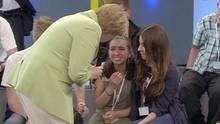 Angela Merkel im grünen Blazer beugt sich zu einem weinenden Mädchen herunter, das ein anderes Mädchen im Arm hält.
