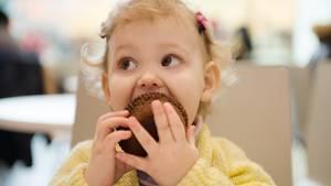 Kleines Mädchen isst einen Muffin
