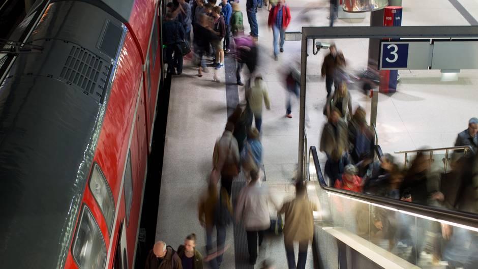 An einem Bahngleis strömen Menschen - verzerrt unkenntlich gemacht - hin und her, auf die Rolltreppe, in einen Zug hinein.