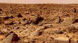 Die Marsoberfläche mit rostig-roten Steinen und Geröll. Der Himmel schimmert rötlich-braun