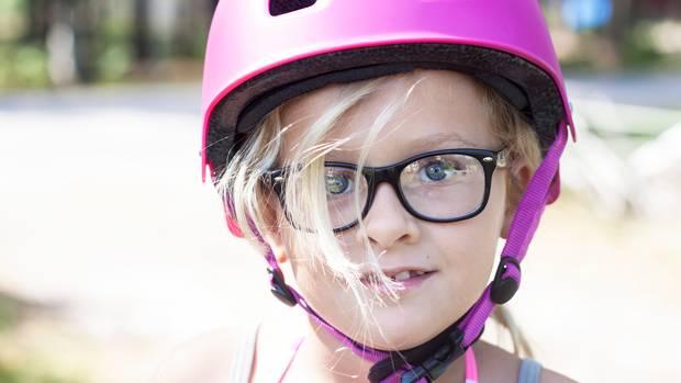 Ein blondes Mädchen mit pinkfarbenem Fahrradhelm