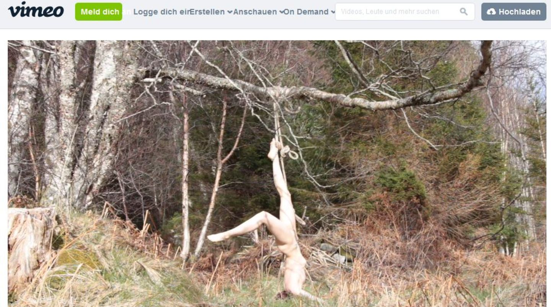 Die Künstlerin Hilde Krohn Huse hängt nackt an einem Baum