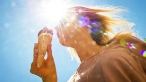 Eine Frau steht im Gegenlicht der Sonne und isst ein Eis