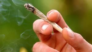 Ein Mann hält einen Joint in der Hand
