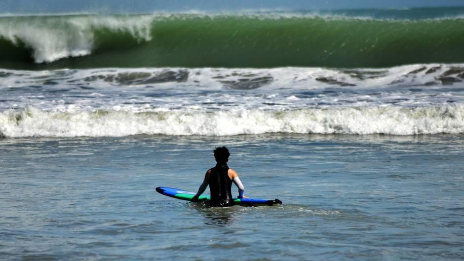 Ein Surfer wartet im Wasser auf die nächste Welle