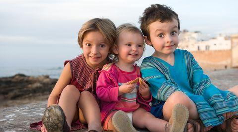 Drei junge Geschwisterkinder sitzen auf einem Hügel