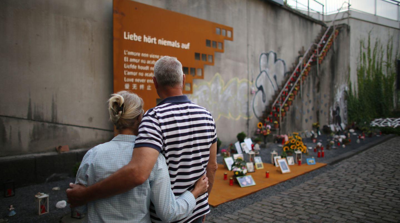 An der Gedenkstätte für die 21 Toten der Loveparade 2010 in Duisburg steht am 5. Jahrestag des Unglücks ein Paar Arm in Arm.