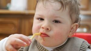 Ein kleiner Junge isst eine Nudel