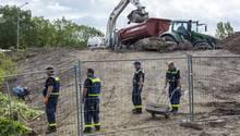 Ein Bagger lädt Schutt in den Anhänger eines Treckers, während im Vordergrund vier Mitarbeiter des THW stehen