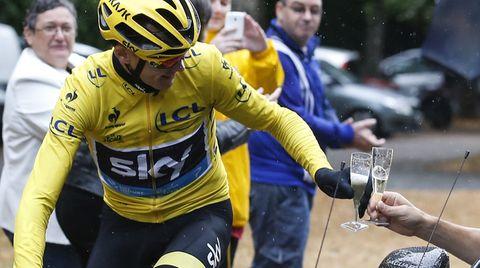 Christopher Froome, Tour de France-Sieger 2015, stößt vom Rennrad aus mit einem Glas Champagner