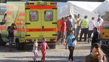 Ein Rettungswagen steht vor mehreren weißen Zelten auf sandigem Boden. Mehrere Erwachsene und Kinder stehen daneben.