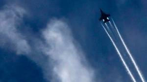 Ein Kampfjet vor bewölktem Himmel, zieht Kondensstreifen nach sich