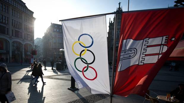 Flaggen mit den Olympischen Ringen und dem Wappen von Hamburg hängen neben einem Straßenkaffee am Rathausmarkt in Hamburg.