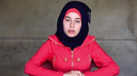 Die 18-Jährige trägt einen roten Anorak und ein schwarzes Kopftuch