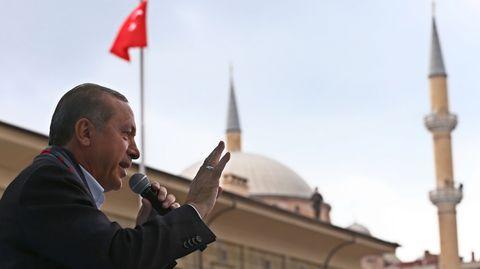 Präsident Tayyip Erdogan spricht in Eskisehir vor einer türkischen Flagge in ein Mikrofon und gestikuliert.