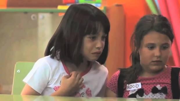 Zwei Mädchen schauen erschrocken auf ein Werbeplakat