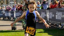 Ohne seinen Gehwagen überquert der achtjährige körperbehinderte Bailey Matthews die Ziellinie