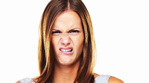 Eine junge Frau verzieht das Gesicht in Ekel