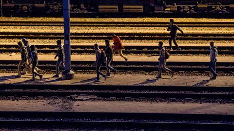 Migranten laufen entlang von Bahnschienen beim Eurotunnel-Terminal