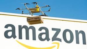 Amazon Prime Air: Eine Lieferdrohne mit einem Paket fliegt vor dem Amazon-Logo